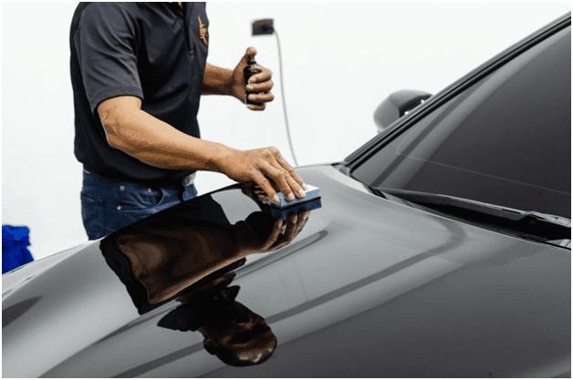 mechanic applying ceramic coating on a black car
